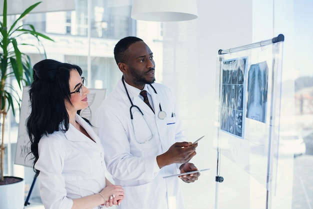 Two doctors look at an x-ray and discuss the problem. medical technicians pointing at mri x-ray of patient. radiologist checking x-ray. medical and radiology concept.