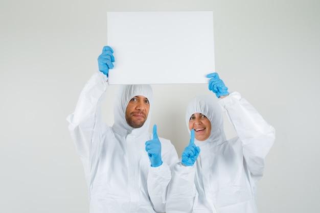 防護服で空白のキャンバスを指している2人の医師
