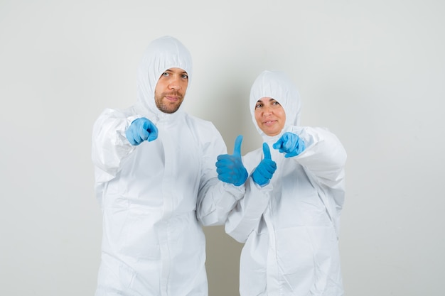 カメラを指して、防護服を着て親指を立てている2人の医師