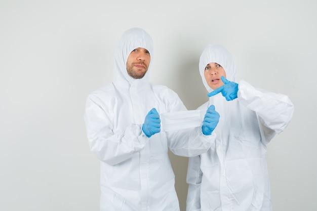Два врача, указывая на медицинскую маску в защитных костюмах