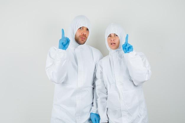 防護服で指を上に向ける2人の医師