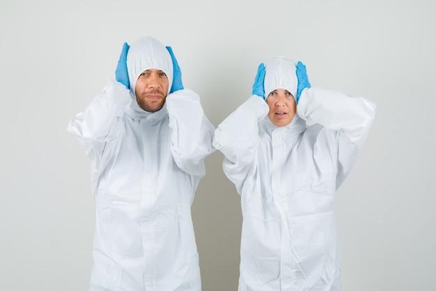 Due medici in tute protettive, guanti che stringono la testa con le mani e sembrano confusi