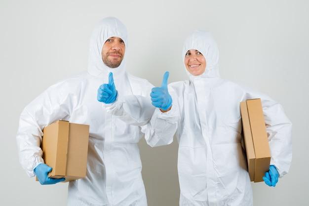 Due medici in tute protettive, guanti che tengono scatole di cartone