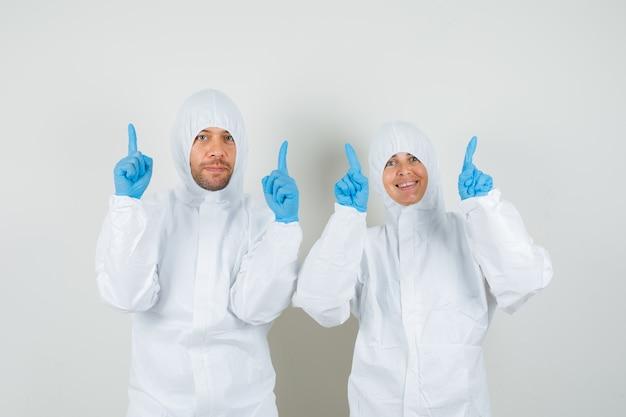 Due medici in tute protettive, guanti che puntano il dito verso l'alto e che sembrano felici