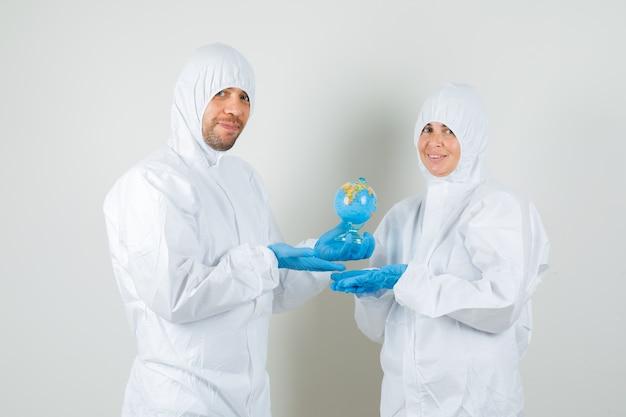 보호 복에 글로브 모델을 보여주는 두 의사