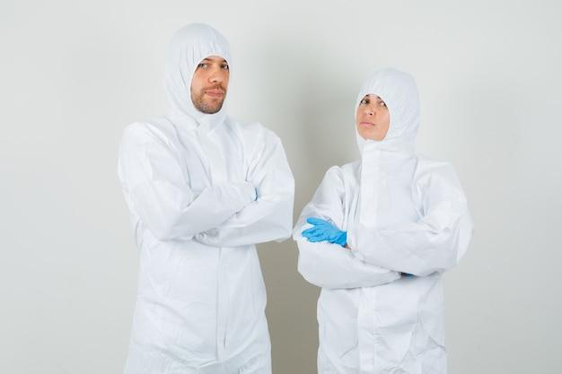 Due medici in piedi con le braccia incrociate in tute protettive