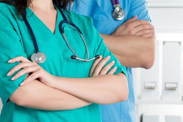 Два врача, скрестив руки на груди, готовы к работе. здравоохранение и медицинская концепция.