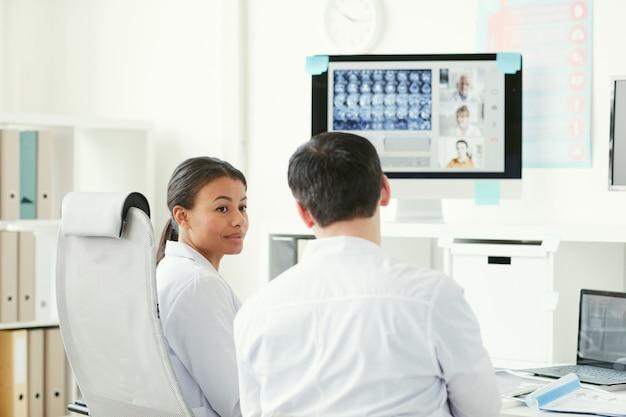 Два врача разговаривают друг с другом, сидя за столом и рассматривают рентгеновские снимки в офисе
