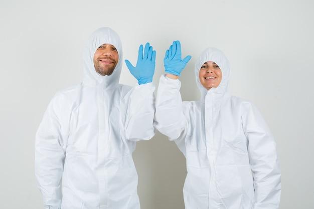 防護服で挨拶のために手を振っている2人の医師