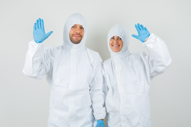Two doctors waving hands to say hello or goodbye in protective suits