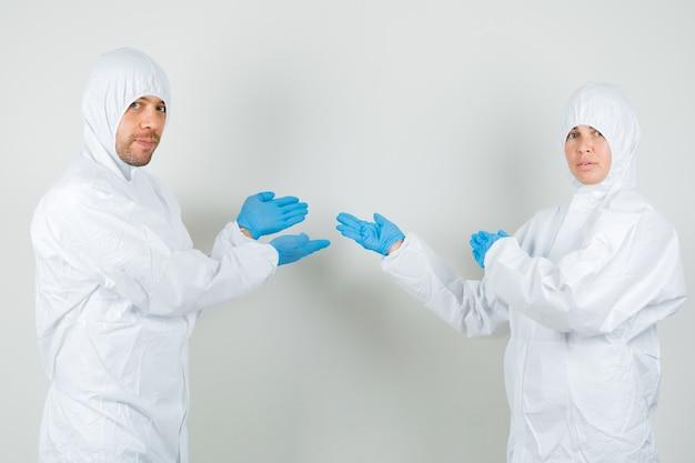 防護服で何かを歓迎または見せている2人の医師