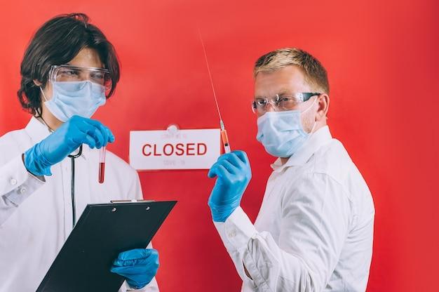 파란색 장갑, 안면 마스크 및 흰색 코트를 입은 두 의사가 빨간색 공간에 대해 테스트 튜브에서 혈액 검사를 확인합니다.