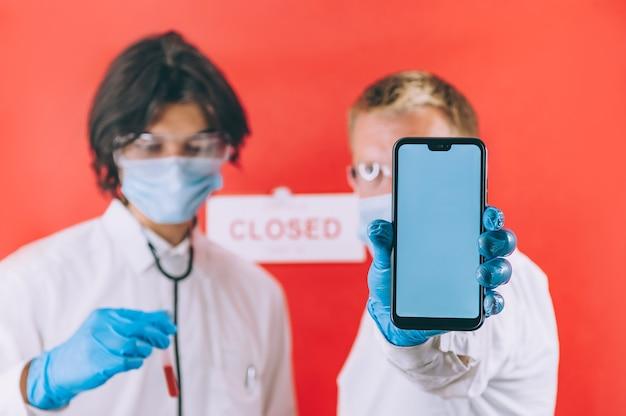 파란색 장갑, 안면 마스크 및 흰색 코트를 입은 두 의사가 손에 스마트 폰을 들고 혈액 검사를 확인합니다.