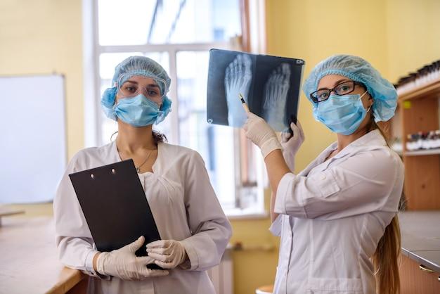 카메라를 위해 포즈를 취하는 의료 실험실에서 엑스레이를 가진 두 명의 의사