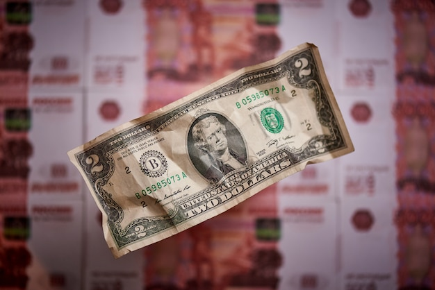 Two dollars on a blurred background of a banknote of the national currency of the russian federation.