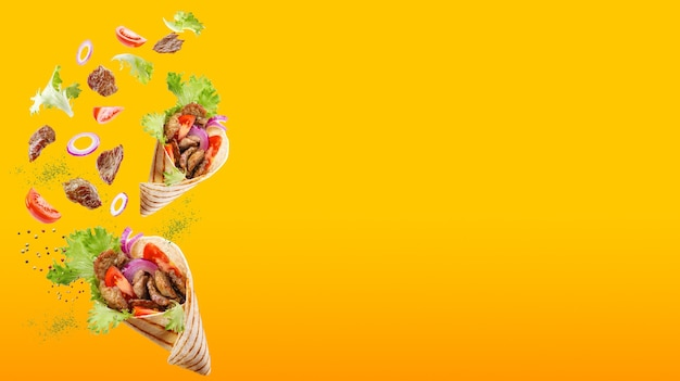 Two doner kebabs or shawarmas floating around with ingredients isolated on gradient orange background