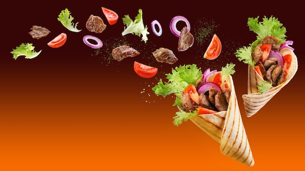 Two doner kebabs or shawarmas with ingredients floating in the air on orange gradient background