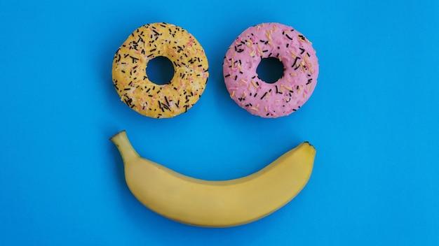 2つのドーナツとバナナが青い表面にあり、絵文字の抽象化を形成しています-笑顔。トップポイントから撮影