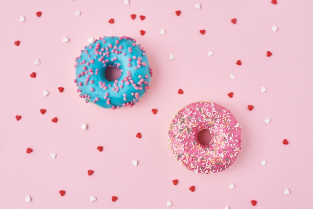 Two donuts decorated icing and sprinkles and confetti in shape of heart on pink