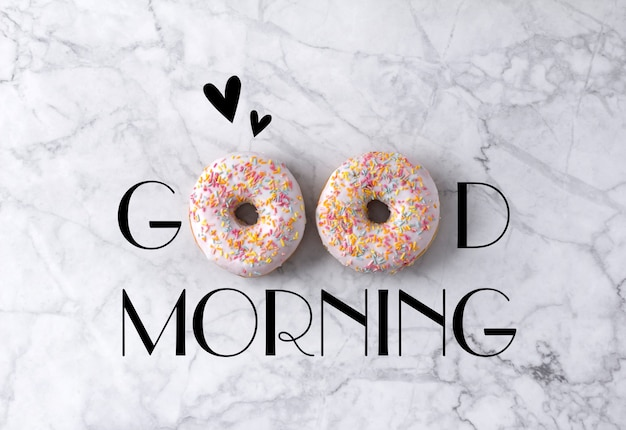 Two donuts and hearts. good morning greeting written on marble gray