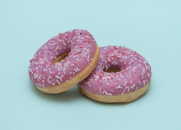 釉薬の青い背景に2つのドーナツ。ペストリー。揚げた甘いデザート。