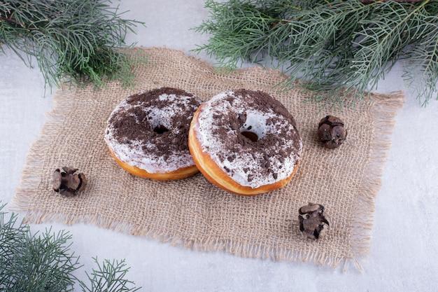 Due ciambelle su un pezzo di stoffa tra rami di pino su sfondo bianco.