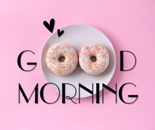 Two donuts on the plate. good morning greeting written on pink