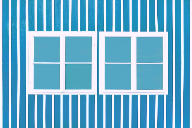 Two double white windows on a blue wall with white slats.