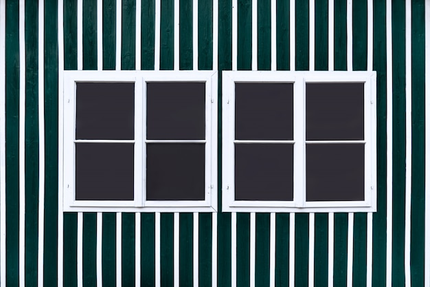Two double white windows on a green wall with white slats.