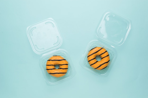 青い背景の開いたプラスチックの配達箱の2つのドーナツ。