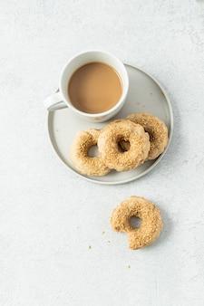 Two doughnuts on white ceramic plate beside white ceramic mug