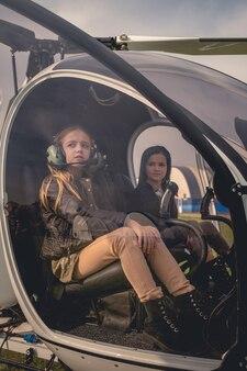 헬리콥터 조종석의 조종사 좌석에 있는 두 명의 꿈꾸는 트윈 소녀