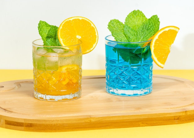 Two drinks on a wooden board orange cocktail and blue cocktail