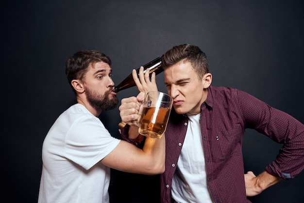 Два пьяных друга пьют пиво отдыхают весело темный фон.