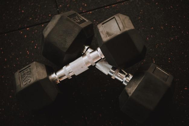 Two dumbbells is lying on black floor in gym