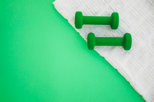 Two dumbbells on white cloth over green background
