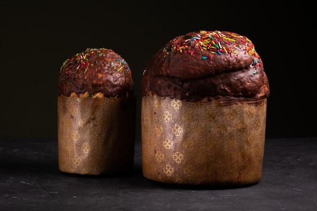 초콜릿을 뿌리고 과자를 뿌린 두 개의 부활절 케이크가 검은 색 표면에 서 있습니다.