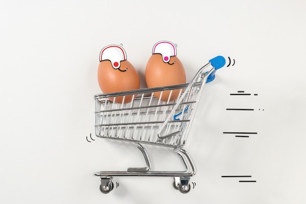 Two easter egg is riding in the shopping trolley and acting like a racers.