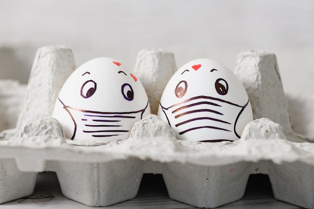Two easter eggs with drawn medical masks