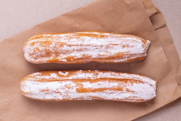 Two eclairs with vanilla cream laying on craft package
