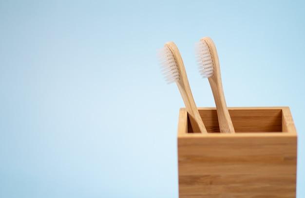 Две экологически чистые бамбуковые зубные щетки в деревянном держателе на голубом фоне с пространством для текста