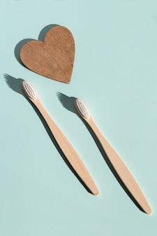 Две экологически чистые бамбуковые деревянные зубные щетки и деревянное сердце на синем фоне ht view