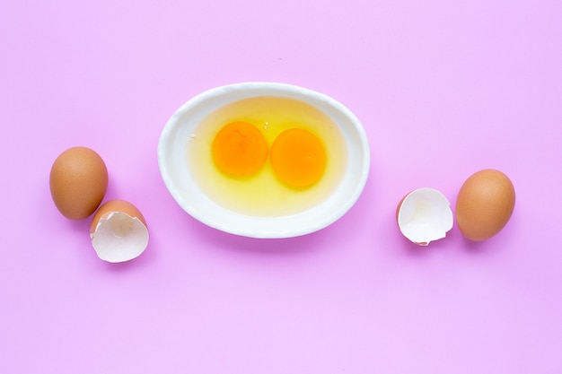 Two egg yolk and white in a bowl on pink