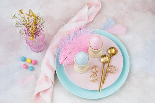 プレートに卵2個とスプーン2個、イースターの装飾と花瓶に花束