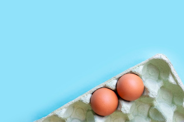 Two eggs in a carton in the corner