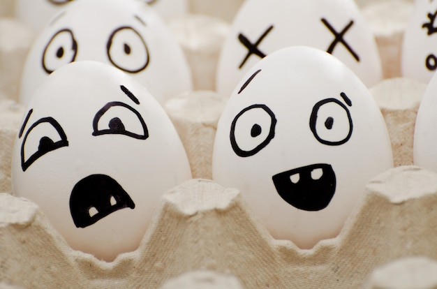 Two eggs with painted emotions: fear and surprise. close-up