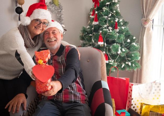 카메라를 보고 붉은 마음으로 선물을 보여주는 산타의 모자와 함께 두 노인과 매력적인 사람들. 백그라운드에서 선물과 크리스마스 트리
