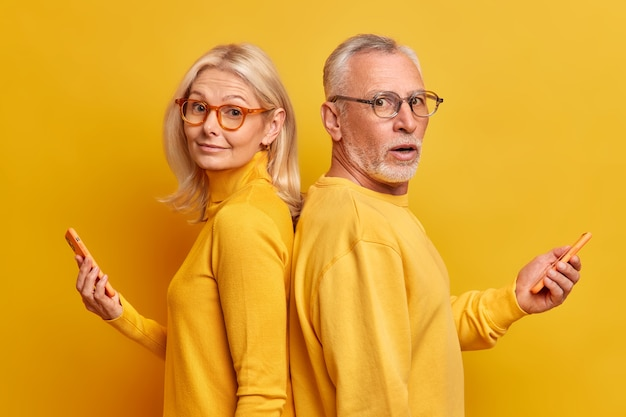 Two elderly female and male friends stand back to each other wear optical glasses casual jumpers use modern gadgets for online communication type text messages isolated over yellow wall