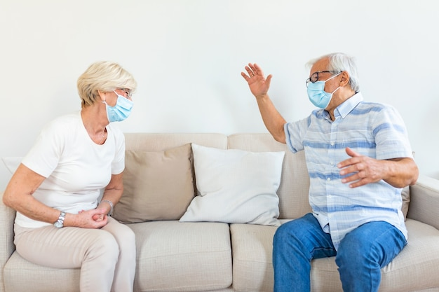 Two elderly friends sitting in social distance wearing medical face mask
