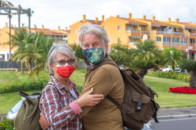Two elderly people on city tour wearing a surgical mask due to coronavirus